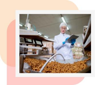 ambiente industrial com alimento em primeiro plano e mulher segurando uma prancheta ao fundo para acompanhar texto sobre registro de alimentos e suplementos
